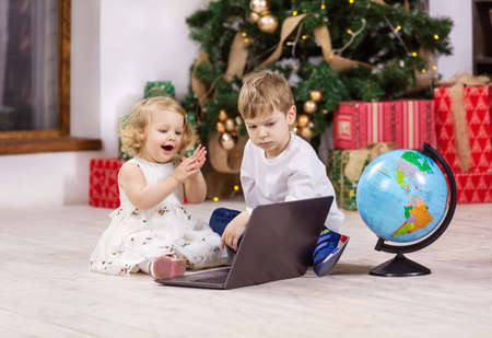 Young girl and boy watching something on laptop computer beside Christmas tree. Globe next to kids. Early education or travel concept.