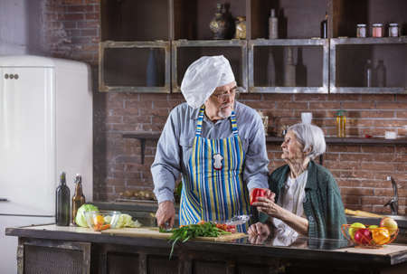 Senior couple cooking together. Man is wearing chef hat and chopping fresh vegetables. Healthy eating habbits. Standard-Bild