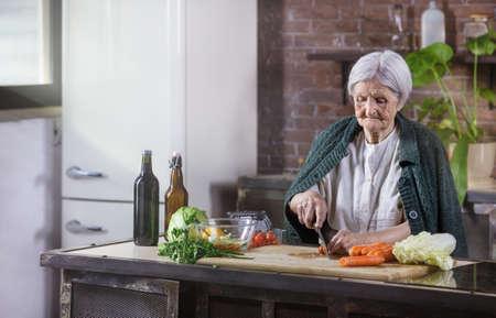 Senior woman chopping fresh vegetables for salad. Healthy eating habits.