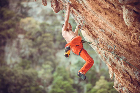 Young male rock climber after jumping and gripping small handholds on overhanging cliff Standard-Bild