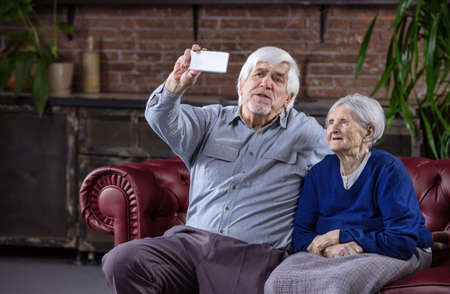 Senior couple taking selfie with smart phone while sitting on couch at home