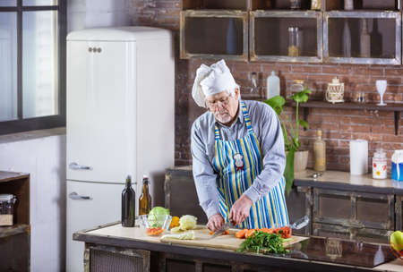 Senior man in chef hat chopping fresh vegetables for salad. Healthy eating habits.