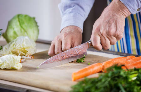 Cropped view of mature man chopping fresh vegetables for salad. Healthy eating habits. Closeup of male hands. Food preparation.