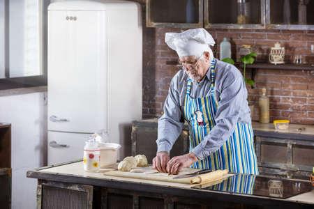 Senior man in chef hat preparing pastries in kitchen at home Standard-Bild