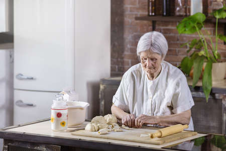 Caucasian senior woman preparing pastries in the kitchen at home