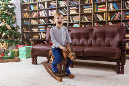 Happy preschool boy on wooden rocking horse, with Christmas tree in background