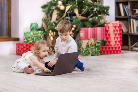 Young girl and boy watching video on laptop computer beside Christmas tree at home