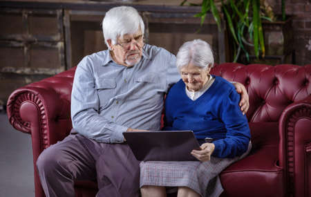 Mature man and senior woman using laptop while sitting on couch. Making video call, watching video or surfing web on laptop.