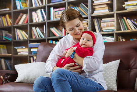 Young woman and her baby daughter on couch in library at home Standard-Bild