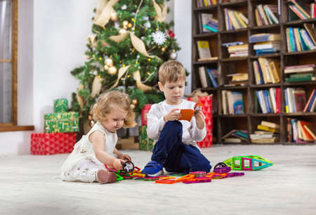 Young girl and boy playing with magnetic toys beside Christmas tree at home
