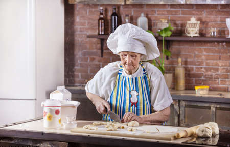 Senior woman in chef hat preparing pastries in kitchen at home