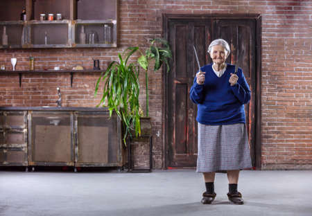 Cheerful senior woman holding kitchen knives indoors. Security and self-defense concept. Could be used in humorous way. Standard-Bild