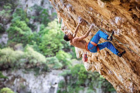 Rock climber on overhanging cliff. Caucasian male climber gripping small handholds on challenging route. Standard-Bild
