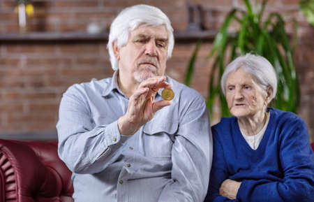Senior couple with bitcoin, man examing or demonstrating bitcoin, woman sitting next to him