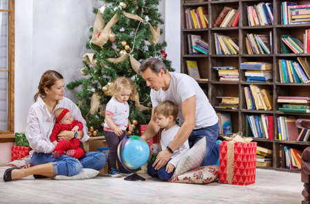 Family with three children beside Christmas tree at home. Kids and father examining globe, mom is holding baby daughter. Standard-Bild