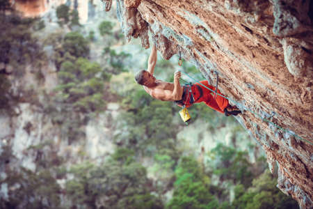 Rock climber clipping rope while climbing challenging route on overhanging cliff. Standard-Bild