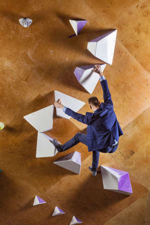 Young man in suit climbing difficult route on artificial wall in bouldering gym. Career challenges concept. Businessman achieving smart goals.