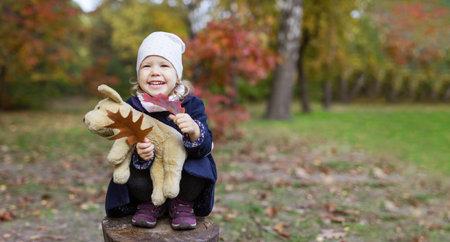 Cute little girl with toy dog in autumn park Standard-Bild