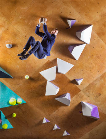 Young man in suit climbing difficult route on artificial wall in bouldering gym. Career challenges concept. The businessman is happy that he has reached the top.