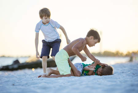 Young boys fighting on beach, older boy going to hit younger one. Siblings rivalry. Standard-Bild