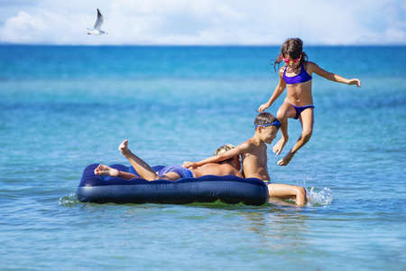 Kids having fun on inflatable air mattress. Young children enjoying summer vacation on seaside.