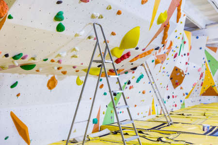 Empty indoor bouldering gym with ladders next to climbing walls. Waiting for setting new routes instead of current ones.