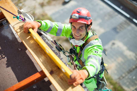 Industrial climber measuring with level tube during construction works, looking at camera and smiling