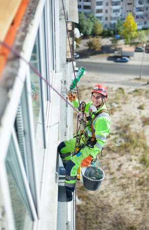 Cheerful industrial climber on building during winterization works, looking up at camera and smiling Standard-Bild