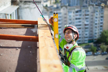 Cheerful industrial climber measuring with level tube during construction works Standard-Bild