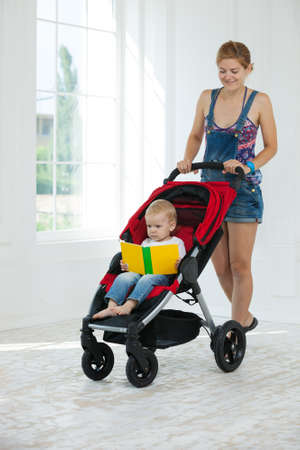 Caucasian young woman and toddler son in stroller indoors. Boy holding book and looking at pictures.
