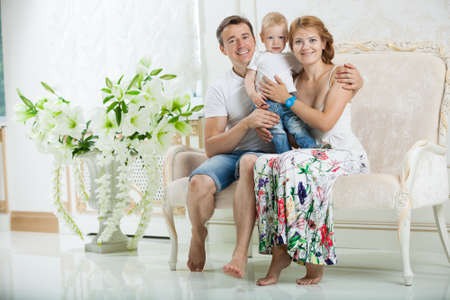 Young happy family with baby boy sitting on couch at home