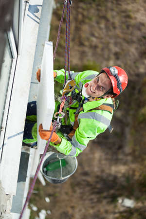 Industrial climber with styrofoam board during winterization works, looking up and smiling Standard-Bild