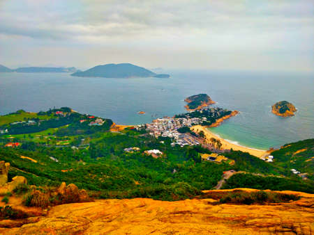 Coastline with sand beach in Hong Kong. There is a deep green forest in the foreground and island and ocean in the background. Sky is cloudy and it seems it might rain anytime.