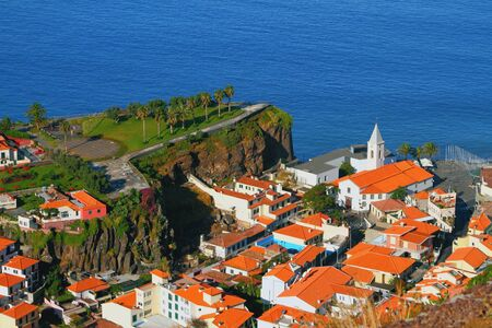 urbanized: Cape rock and town on coast. Camara-de-Lobos, Madeira, Portugal