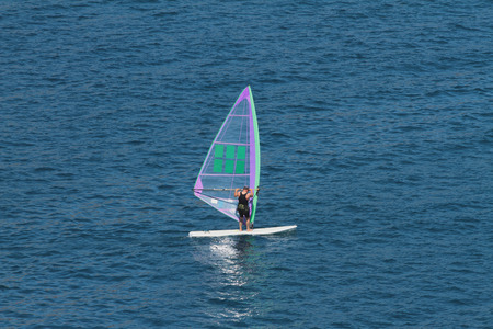 sailboard: Man on board with sail for surfing