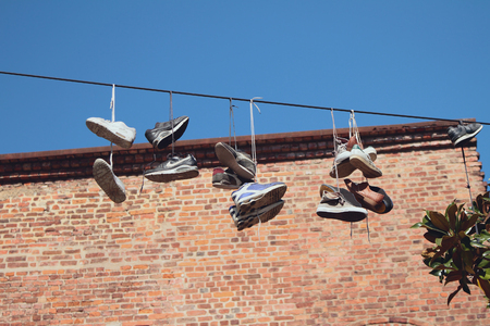 Sneakers hanging on wire. Milan, Italy