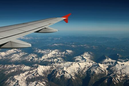 Under plane wing snow-covered mountain tops. Austria-Italy