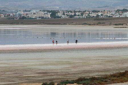 Salty lake and tourists on coast edge. Larnaca, Cyprus