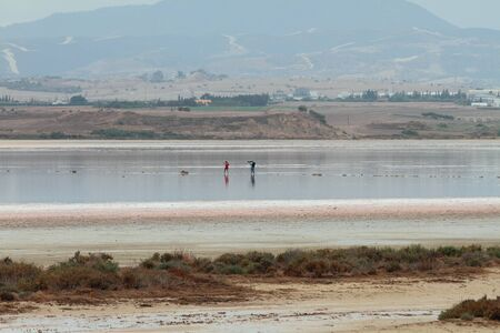 Salt lake and photographer with model in middle. Larnaca, Cyprus