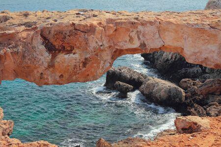 Natural stone arch on sea coast. Cape Greco, Aya Napa, Cyprus