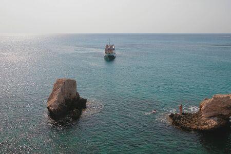 Rocks and pleasure boat in sea. Agia Napa, Cyprus Stok Fotoğraf
