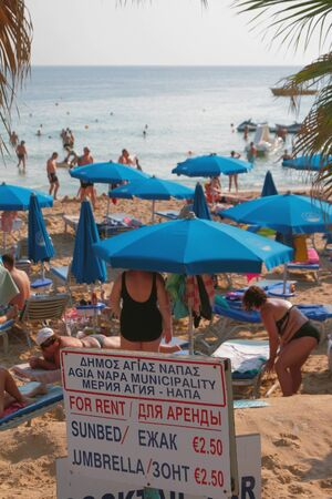 Agia Napa, Cyprus - Oct 26, 2019: Beach stand with cost of beach sunbeds and umbrella