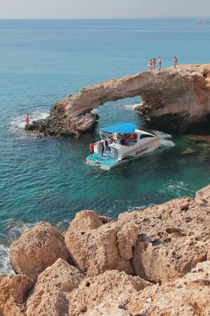 Agia Napa, Cyprus - Oct 26, 2019: Walking boat next to rock arch