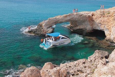 Agia Napa, Cyprus - Oct 26, 2019: Walking boat and rock arch