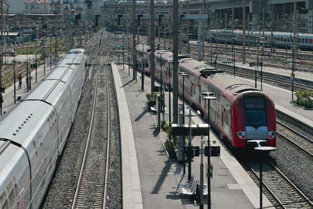 Nice, France - Apr 19, 2019: Electrified railway tracks and trains at station