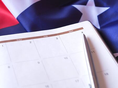 The pen point to number 4 in a diary, put on the American flag background.