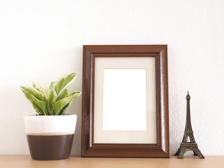 Brown border photo frame and little tree on a wooden shelf with a white wall as the background. Archivio Fotografico