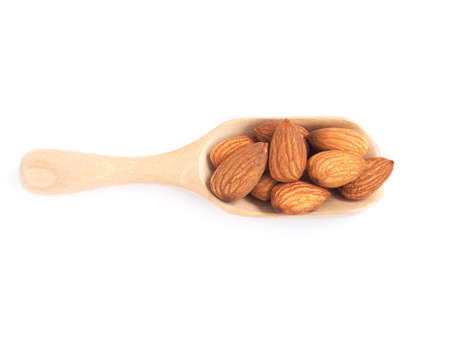 Almonds seed in wooden scoop isolated on a white backgound. Healthy food.view from above.