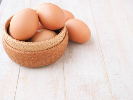 Organic egg in wicker basket on white wooden background. High protein and Vitamin foods. Concept food of healthy.