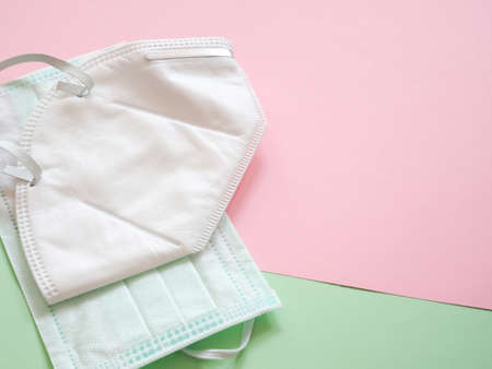 2 medical face masks stacked on a green and pink background. There is a copy area on the right. Health protection concept.